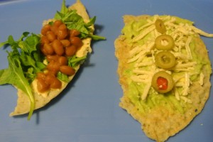 Juliet sized wraps - one half with hummus, baby arugula & homemade brown beans, the other half with guacamole, Diaya cheese & olives